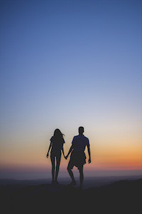 couple-holding-hands-at-sunset